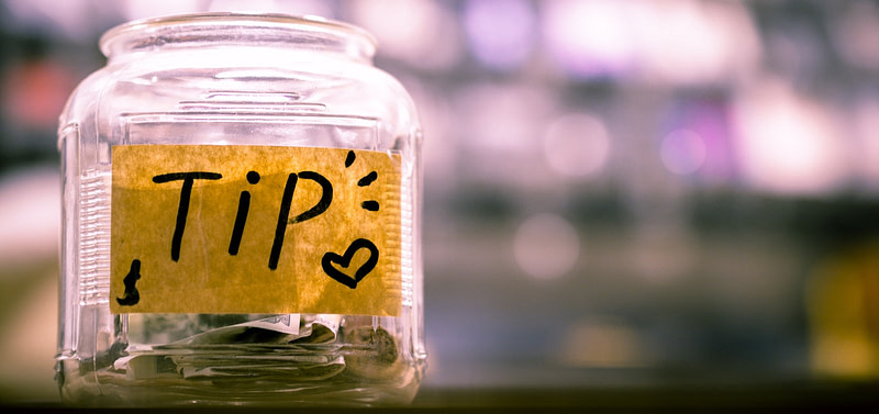 Image of a glass jar used for tips, showing money already put inside.